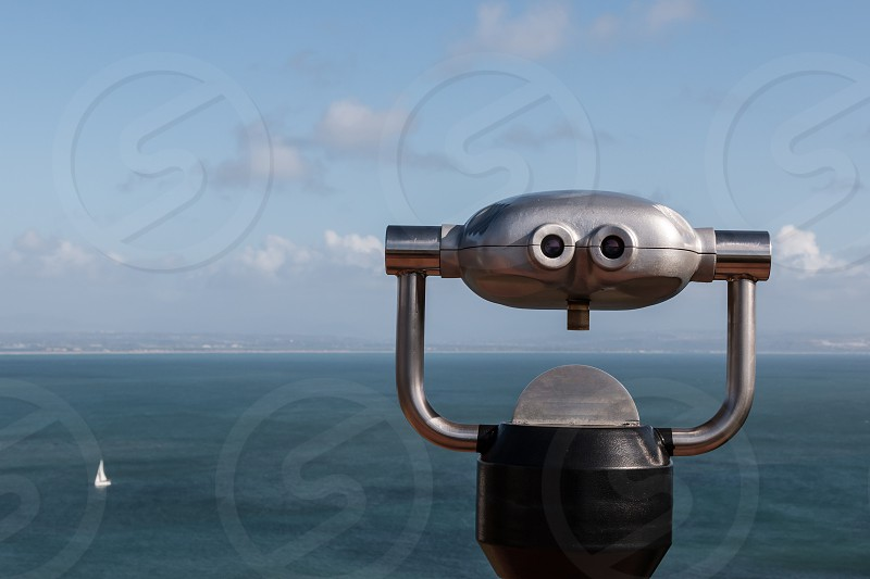 Sightseeing binoculars overlooking the ocean with a single sailboat in the distance.  photo