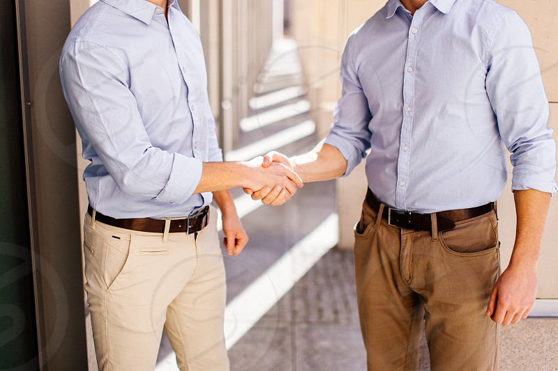 Two businessman shaking hads to each other with street city blur background photo