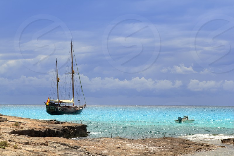 pirates inspired wood sailboat anchored turquoise sea Formentera photo