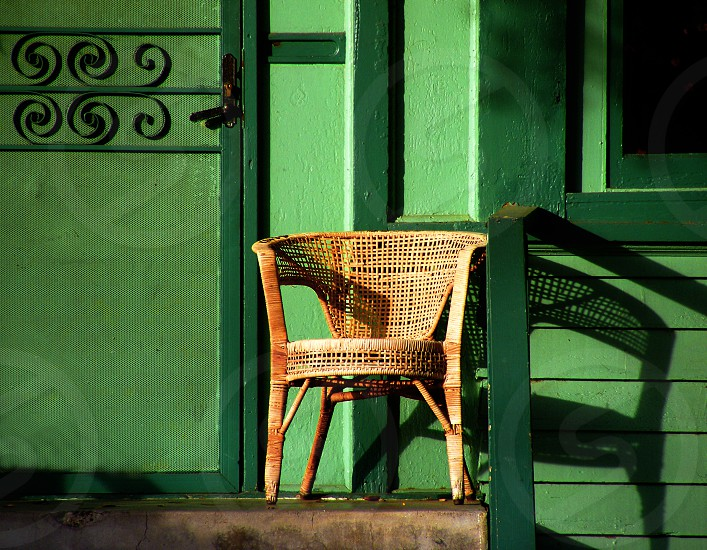 A tan wicker chair stands on a top step near the front door of a bright green home. photo
