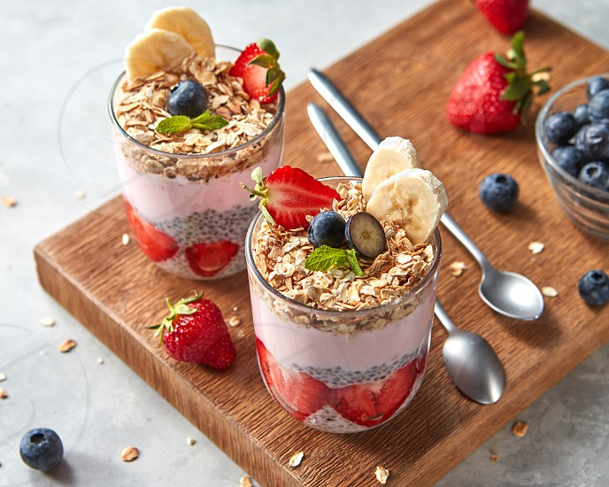 Healthy pink smoothie in glasses with natural fruits: strawberry banana blueberry oat flakes and chia seeds on wooden board on grey background. Superfoods natural detox diet and healthy food. photo