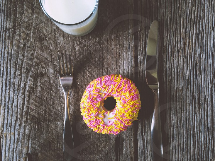 Sprinkle Donut with Knife & Fork Glass of Milk On Barn Wood photo