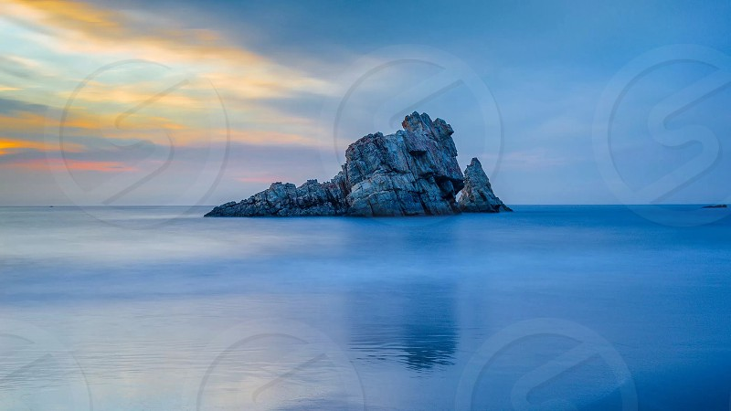 gray rock in the middle of the sea photo
