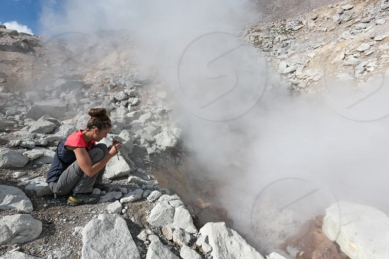 NALYCHEVO NATURE PARK DZENZUR VOLCANO KAMCHATKA PENINSULA RUSSIAN FAR EAST - SEP 04 2014: Beautiful young woman photographing steaming (smoking) fumarole on crater active Dzenzur Volcano. photo