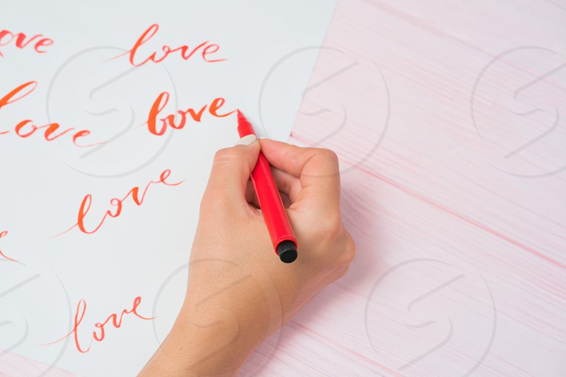 Calligrapher student practices in writing word LOVE with red marker on canvas. Creative artist freelancer working on project at home studio. Lettering handwriting concept. photo