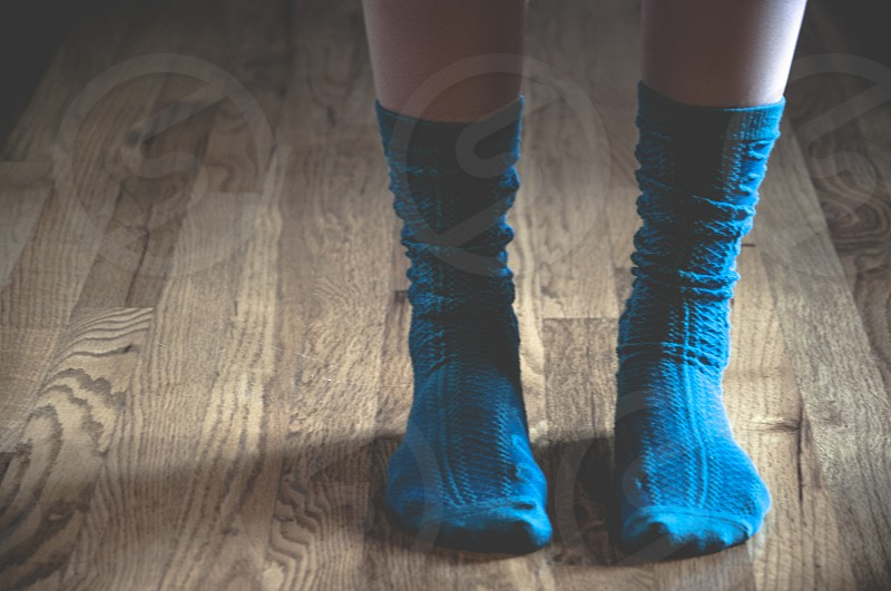 person wearing blue socks standing on a wooden floor photo
