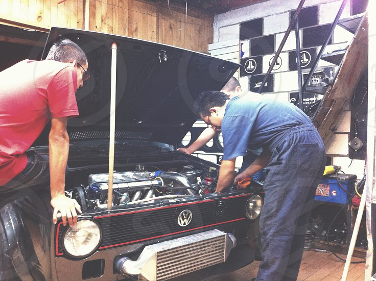 man in blue shirt standing in front of Volkswagen engine bay photo