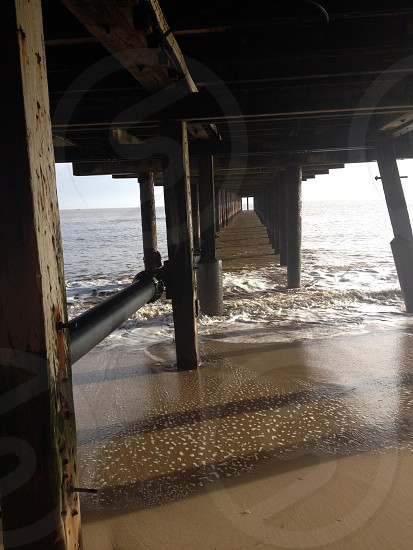 Under a wooden pier on a beach photo