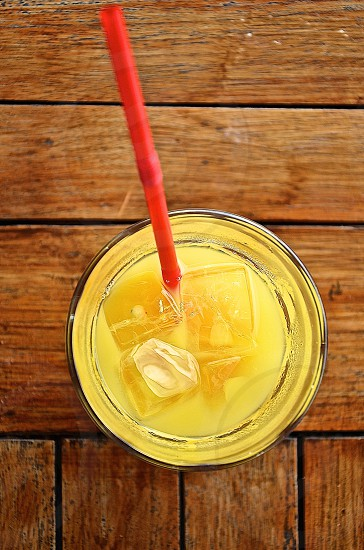 clear drinking glass half-filled with yellow liquid with ice cubes and red straw on top of brown wood surface photo