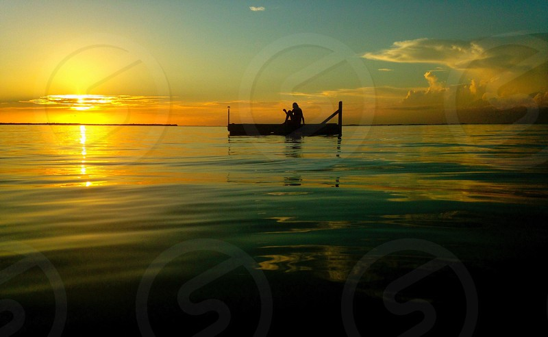 silhouette of person on row boat on body of water during sunset photo