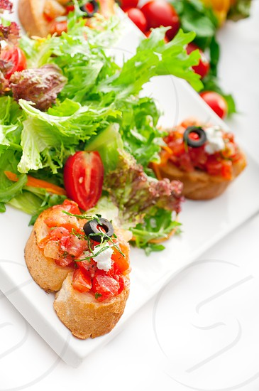 original Italian fresh bruschettatypical finger food with fresh salad and vegetables on backgroundMORE DELICIOUS FOOD ON PORTFOLIO photo