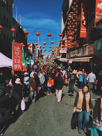 people walking by the stalls on the street with red and gold lanterns and kanji banners photo