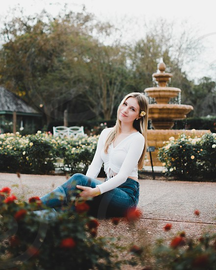Girl model sitting by fountain and roses photo
