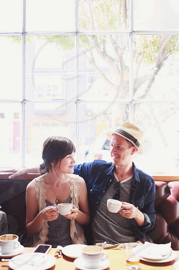 2 people sitting on couch drinking coffee photo