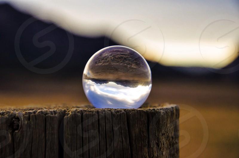 crystal round ball on tree log during daytime photo
