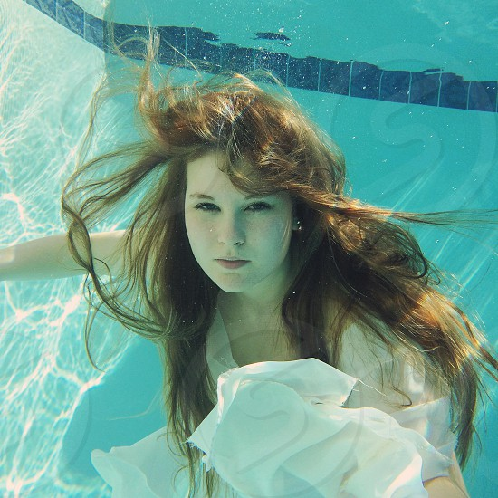 woman with long hair in white dress in underwater photography photo