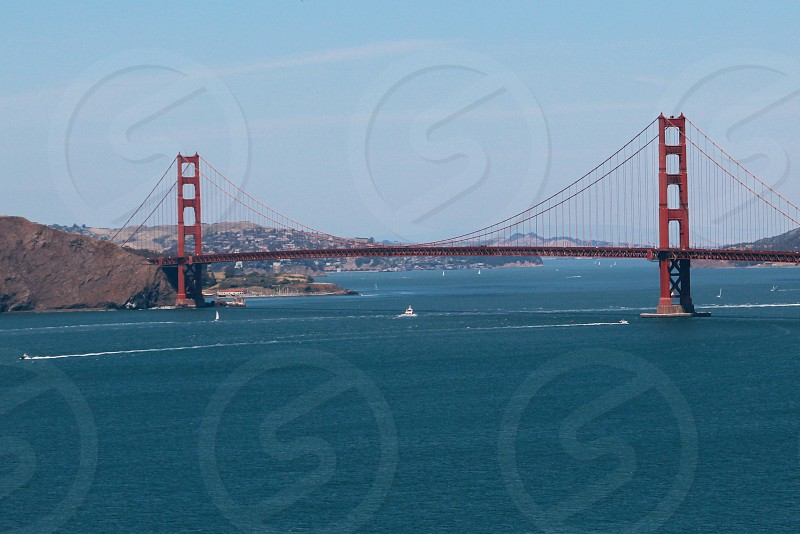 san francisco golden state bridge under clear blue sky with overlooking view of mountains and boat on body of water photo