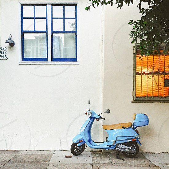 Blue Vespa in front of white wall  photo