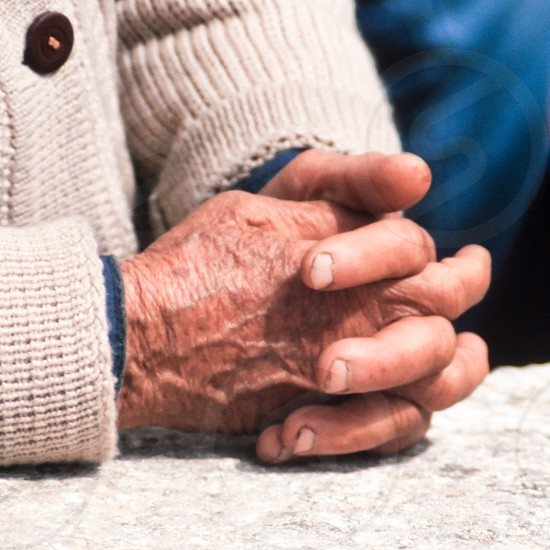 Folded hands of old working person waiting closeup detail photo