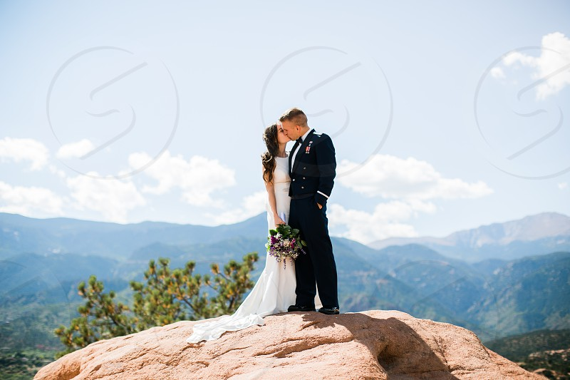 bride and groom on rock in mountain setting photo