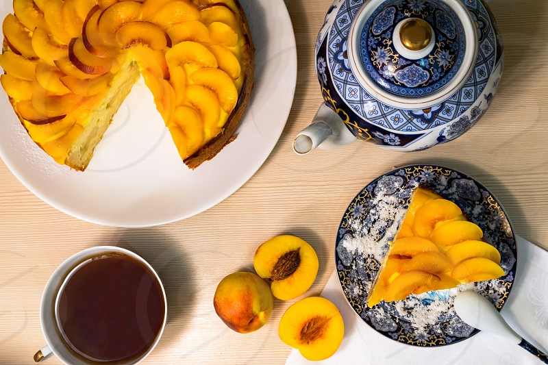 Composition with tea and peach cake  on the table photo