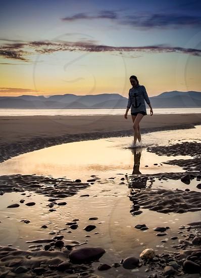 woman in grey longsleeves walking seaside photo