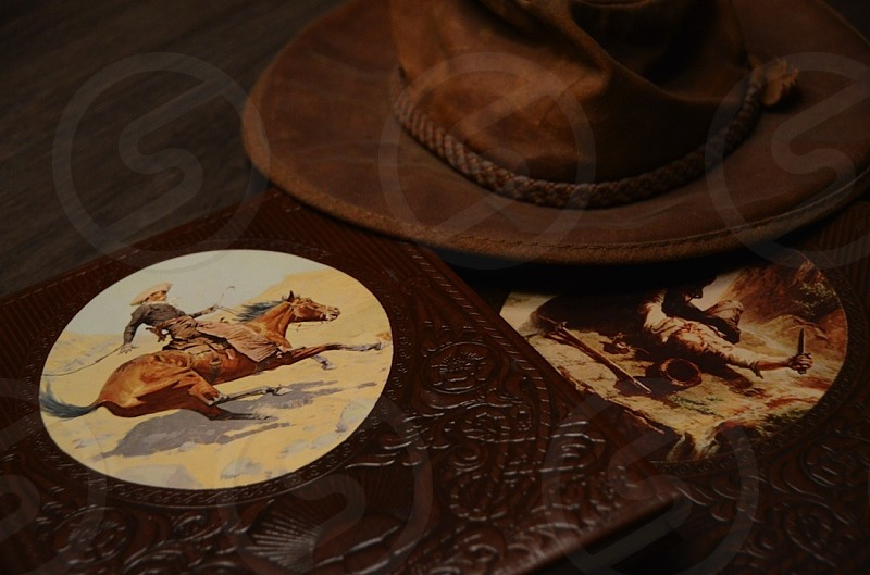 brown leather cowboy themed notebook beside brown cowboy hat photography photo
