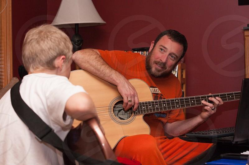 guitar lesson; guitar; man and boy; man and boy practicing guitar; guitar practice; learning guitar; guitar; acoustic bass guitar; bass guitar; 6 string guitar; Fender Strat photo