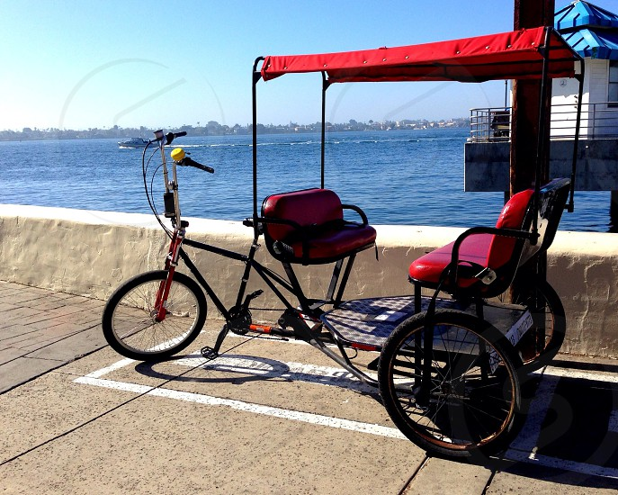 Bike taxi seaport taxi red bench bicycle tri-cycle wheels spokes bell peddles photo