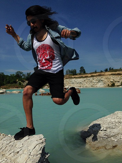 man in white black and red tank top and blule jacket and black bermuda shorts jumped on the grey rock photo