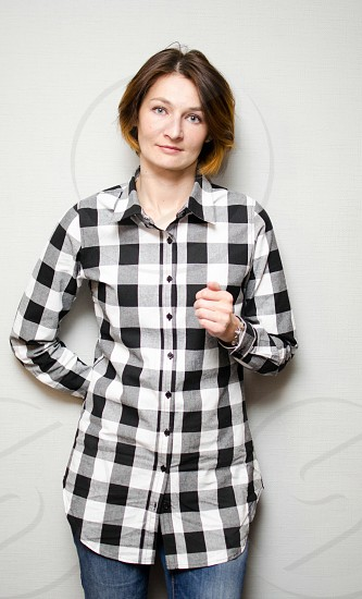 Pretty young woman wearing checkered shirt and jeans photo