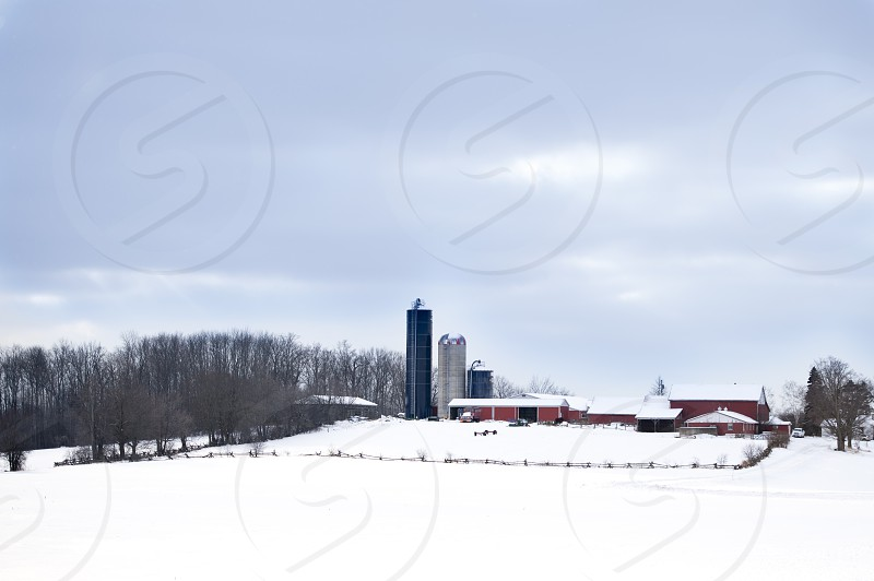 Winter Farm Scene with Red Barn in Distance photo