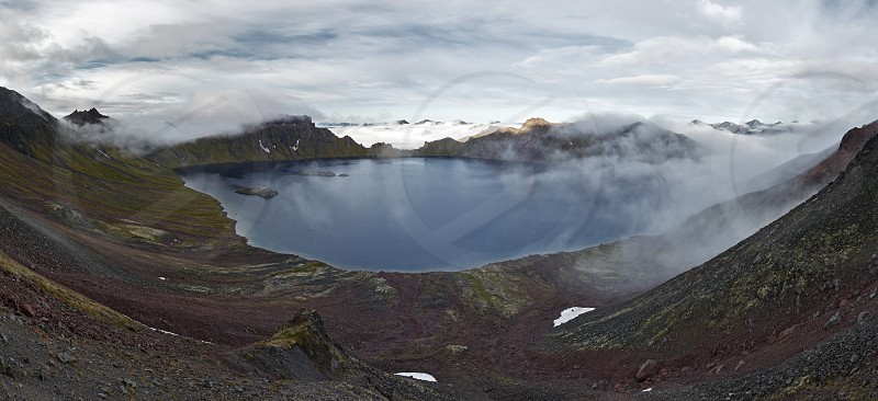 Natural beauty of Kamchatka: summer panoramic view of crater lake active Khangar Volcano in cloudy weather. Kamchatka Peninsula Far East Russia. photo