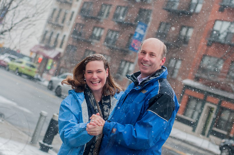 smiling couple in blue jacket standing holding hands on sidewalk photo