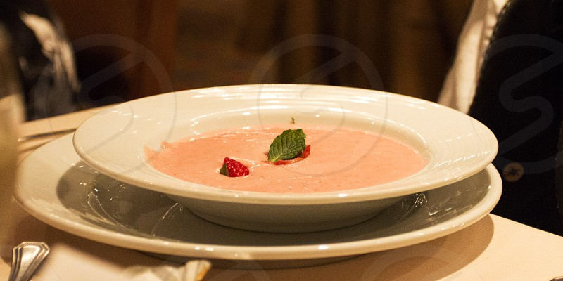 Strawberry soup in white bowl on white plate photo