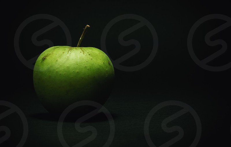 Details of one green apple on dark background.  photo