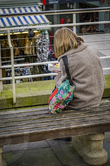 Woman sitting on a bench eating chips photo