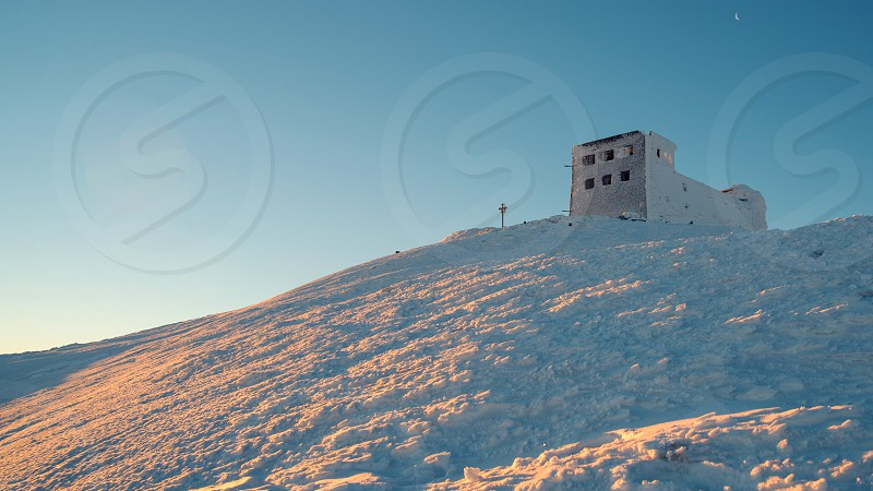 Buildings on the top of Snezka mountain during winter sunrise photo