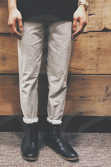 photo of man wearing gray corduroy pants and black leather boots photo