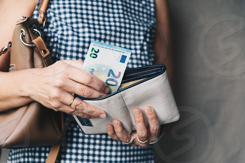 Closeup photo of stylish woman taking money out the wallet photo