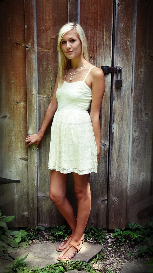 woman in white sun dress standing in front of wooden fence photo