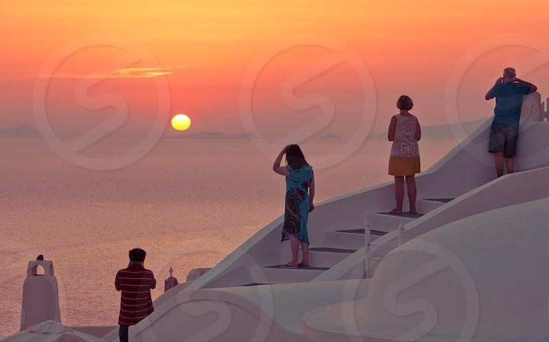 People Enjoying Sunset On Famous Greek Island Santorini photo