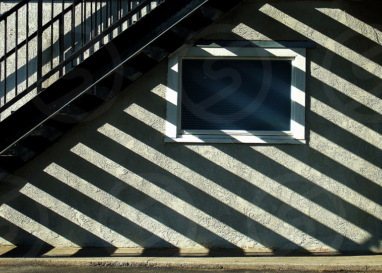 Light shines through an outside stairway creating parallel shadows on a building wall. photo