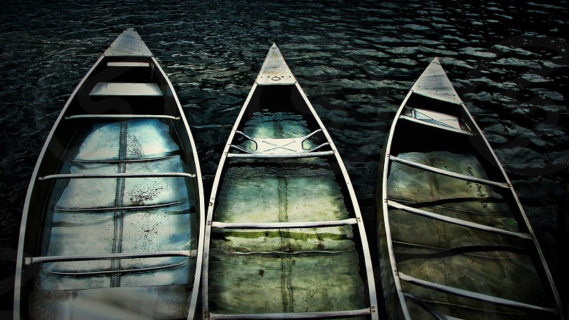 three canoes in the rain floating on a Northeast Georgia lake in the mountains photo