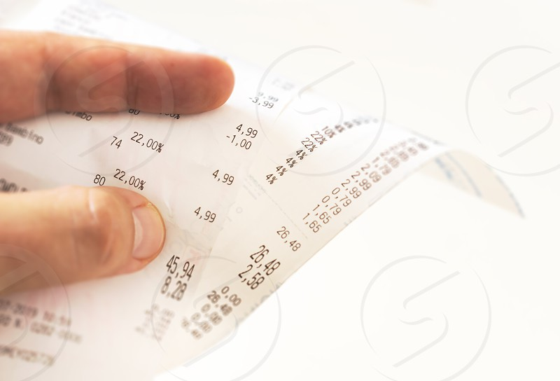 human fingers holding a paper receipt with the bill of charges and checking the total amount. Domestic finance. Tax receipt on a roll of thermal paper photo