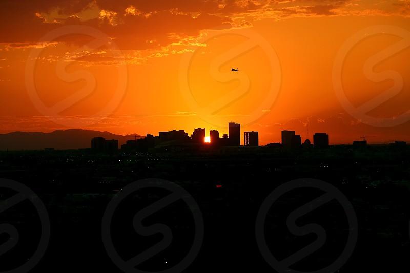 Travel airplane city skyline Arizona Phoenix sunset sun orange fiery fire Sky summer vacation USA United States buildings downtown fly flying leisure desert winter escape air photo