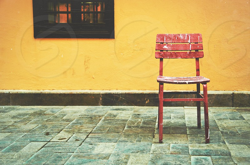 A red chair in an alleyway. photo