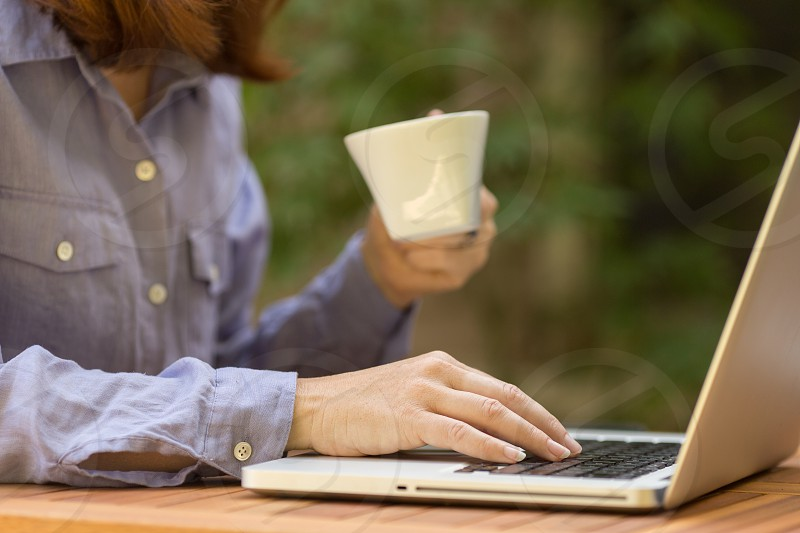 A woman drinking a cup of tea or coffee while working on her laptop at an outdoor table. photo