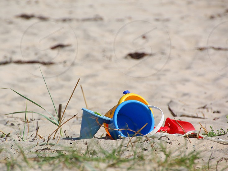 Beach sand abandoned plastic toys spade buckets red blue yellow photo