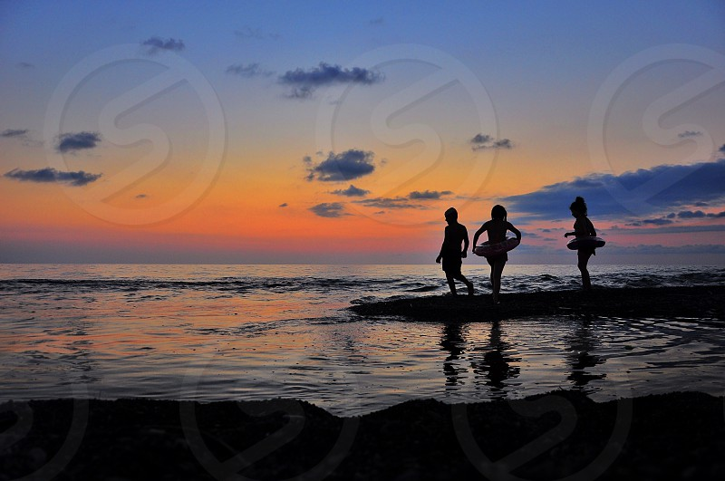 3 children standing on beach seashore photo